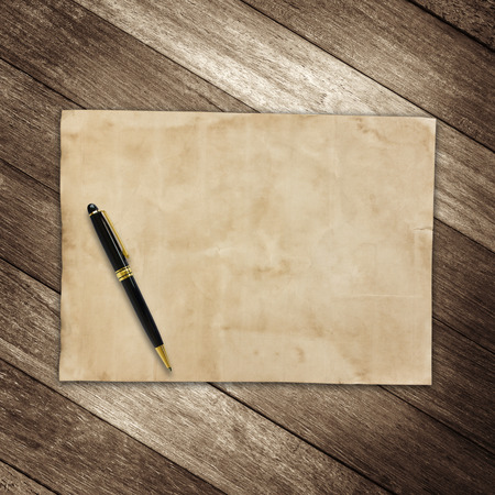 old brown paper and pen on wooden wall background for texture photo