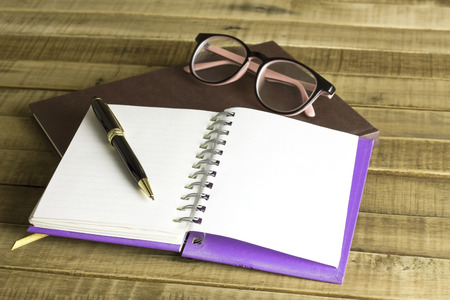 actuality: book with glasses and pen on the wooden background.