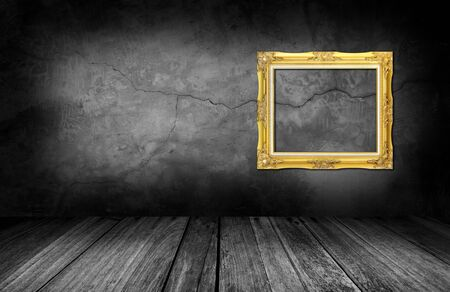 antique frames: gold frame on gray stone wall background in interior room.