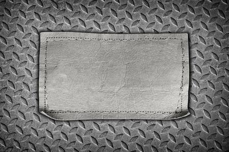 diamondplate: jeans labels on steel plate background.