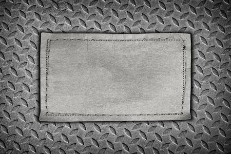 diamondplate: jeans labels on steel plate background.