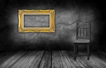 antique frames: gold frame and wood chair in interior room with gray stone wall.