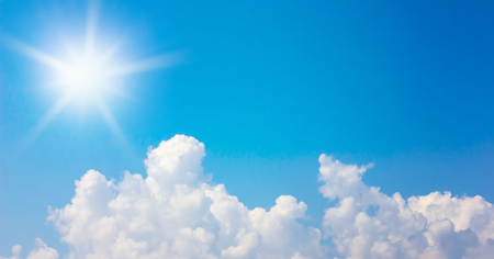 clouds and sun in the blue sky background. Stock Photo