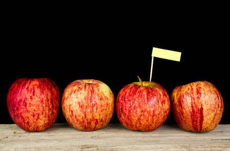 Red apples and yollow label put on wooden with black background