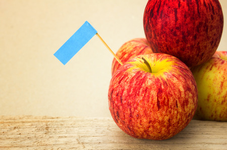 Red apples and blue label put on wooden with paper as the background
