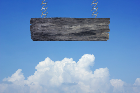 wood sign on clouds in the blue sky background.