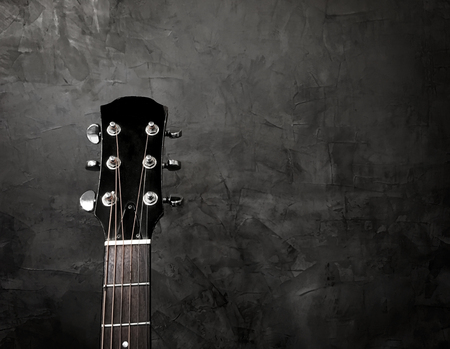 Close up acoustic guitar on a black background, with copy space for texture.