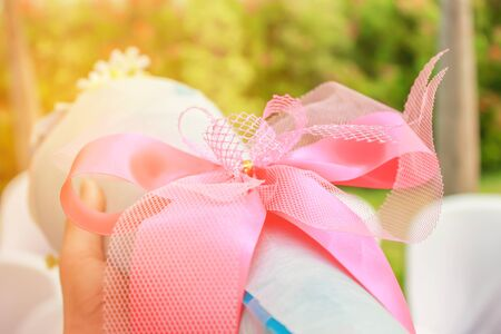 Pink bow on a bouquet of flowers is given as a gift.