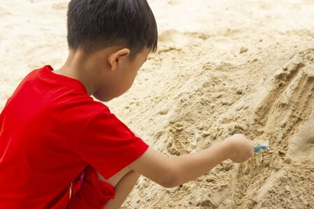Boy playing with a shovel in a sand. Child building sand in the playground.
