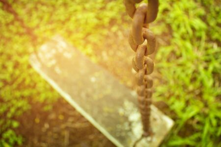 Close up of old chain on swing set in playground.