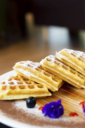 Homemade waffles with berries in plate on table at cafe. Stock Photo