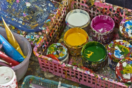 Cans  tins  with colour oil paints and brushes in press photo
