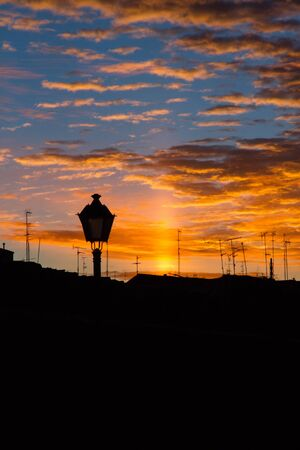 Backlight at first light with the morning sun on the rooftops of the old city  With streetlight in the foreground  Leon  Spain  photo