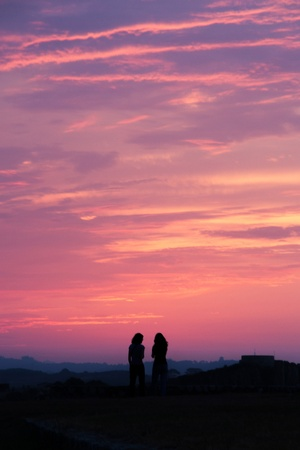 Backlight of a couple of girls  Sunset or sundown  Llanes  Asturias  Spain photo