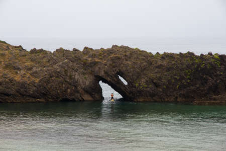 paddler: Paddle Surf paddler crossing a rock arch on the seashore Playa de San Antolin  Asturias  Spain