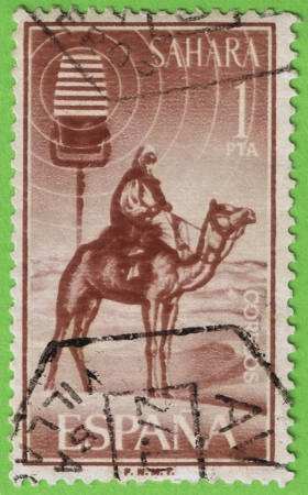 camel post: Old postage stamp used and postmarked in the Sahara  Correos of Spain  Reason  man of the desert on camel  Face value 1 peseta  Edited by the national factory of la Moneda y Timbre
