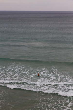 the bather: Solitary bather, between waves, venturing into the vast sea Stock Photo