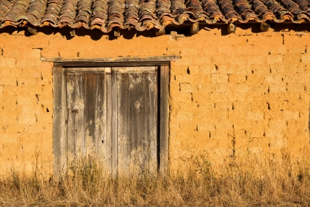 farm implements: tillage hut  Small house or house farm implements  Built of adobe mud and thatched and old wooden door  The setting sun