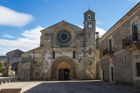 open topped: View of the facade of the Monastery Church Meira, with the door open, rosette central tower topped with a cross, bell and clock  Romanesque style  To the right of the local council, Lugo  Galicia  Spain
