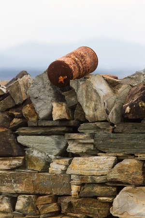 gas cylinder: Barco o cilindro de gas al viejo oxidado pizarra pared de piedra