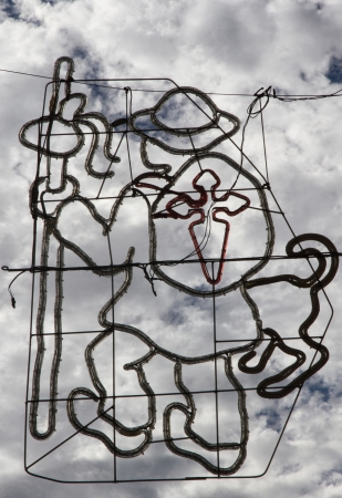 Camino de Santiago ( Way of St. James ) pilgrim accompanied by a dog, stick or cane, and a backpack with the symbol of the Cross of Santiago in red. Design outlines for street lighting at parties on sky background with white clouds