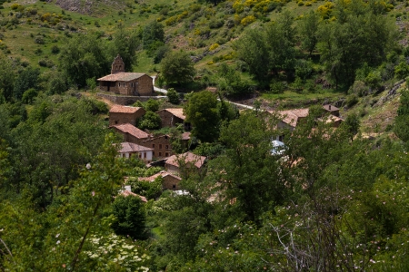 rural town: Beautiful view of small town or rural town of charming mountain spring. Surrounded by flowers, trees and vegetation. Church at the top. La Red. Leon. Spain