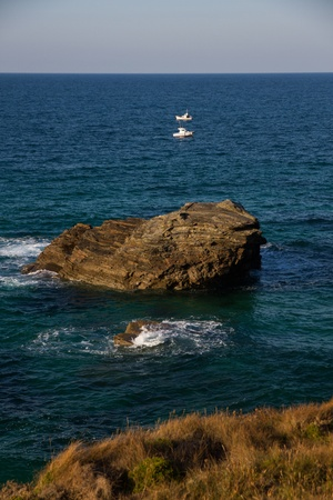 cantabrian: Cantabrian Sea coast in Spain with rocks and two small fishing boats
