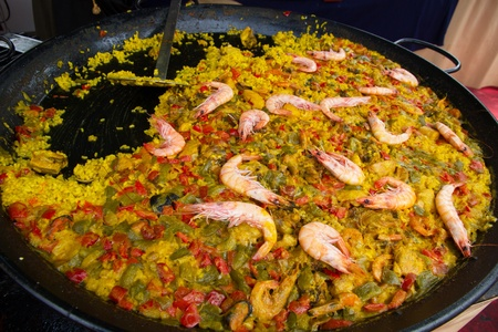 slotted: Paella with seafood rice, fish and vegetable  Shrimp, clams, mussels and green and red peppers as main ingredients  With slotted spoon or ladle to serve rations