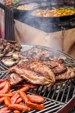 grilled meat and smoke lit outdoor fair  Pork, chicken and beef, sausages  In the background paellas and fruits  Banque d'images