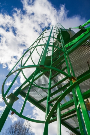 fall arrest: Vertical metal ladder green  Silo for storing road salt overlooking the snow season  Staircase to blue sky with clouds with safety rails and screens landings