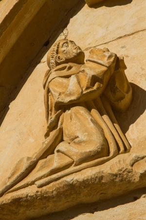 lintel: Figure sculptural praying monk or friar kneeling, carved in stone, located on the lintel of a door of the monastery of the twelfth century Cistercian, Santa Mara de Sandoval  Leon  Spain Stock Photo
