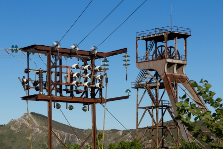 insulators: derrick headframe  tower elevation  of old mine shaft and closed with electrical distribution tower with ceramic and glass insulators  Sotillos  Leon  Spain  Stock Photo