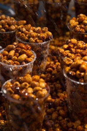 expositor: Cacahuetes chufa en vasos de pl�stico regado con agua en expositor justo