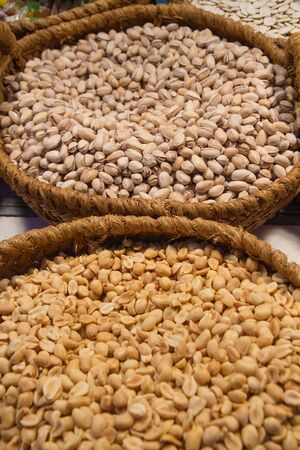 dry fruits: Baskets full of dry fruits in exhibitor  We see pistachio nuts and peanuts  Stock Photo