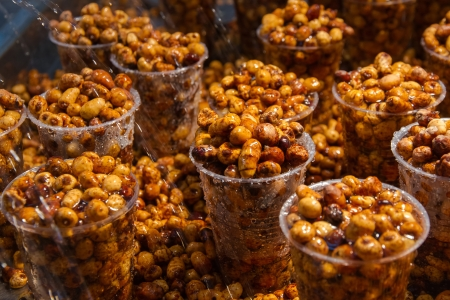 watered: Groundnuts tiger nut in plastic glasses watered with water in fair exhibitor