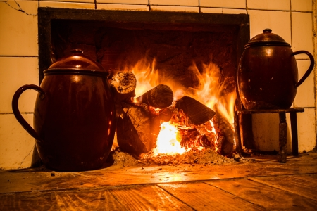 hearth and home: Chimney, kitchen hearth of burning rural house  Fireplace, stove on at home farmhouse  Fireplace, home farmhouse kitchen on  Tint old scene  Cooking pots on trivets two fire Stock Photo