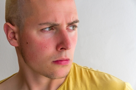 beardless: Close-up portrait of young man with a frown, serious and looking to the side, with yellow shirt