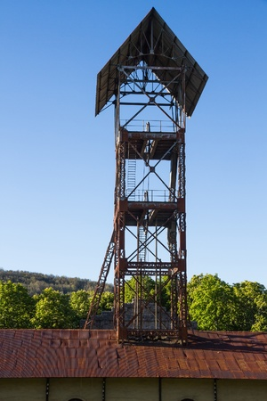 mining ships: headframe   tower elevation   of old hangar mine shaft and closed between trees  and vegetation highland   Leon   Spain
