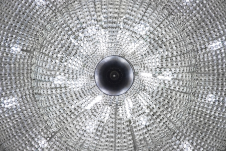Huge circular lamp lighting in theater hall with glass beads strung with metal
