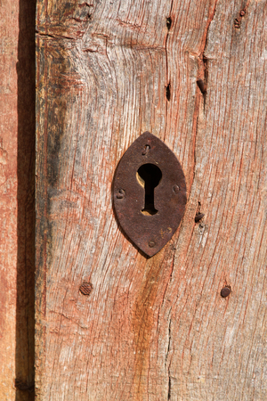 unpainted: Detail of old rusty lock on old wooden door unpainted red  Stock Photo