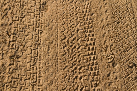 Rolled geometric footprints of vehicles and human footprint on dusty dirt road