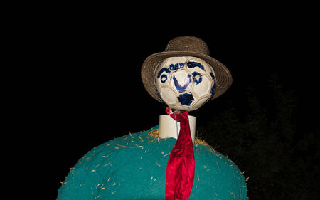 Scarecrow at night with soccer ball head and straw hat  photo
