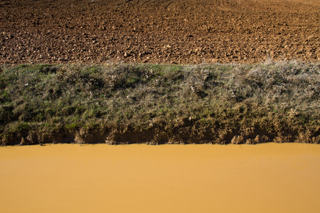 earthy: Natural textures background ocher, brown and green  Landscape of dirt, grass and muddy water