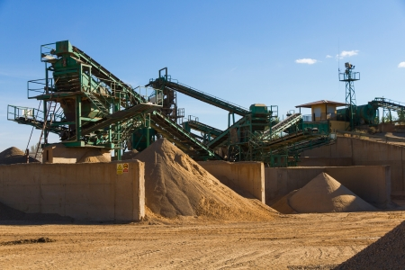 Used gravel pit near the river to mills, conveyor belts and piles of sand - photo