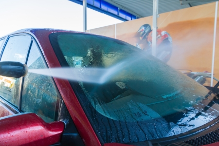 soaping: Washing car windshield with hand-pressure water jet  Stock Photo