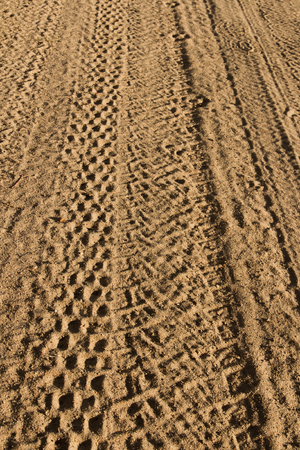Rolled geometric footprints of vehicles on dusty dirt road photo