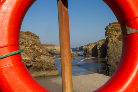 las vistas: Lifeguard Float overlooking the Beach of the Cathedrals   rising tide    Sunset on the rocks of the coast  Lugo  Galicia  Spain - Flotador salvavidas con vistas a la Playa de las Catedrales   subiendo la marea    Atardecer en las rocas de la costa