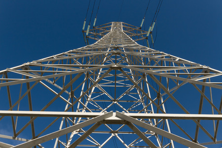 voltage gray: Electricity distribution tower seen from below on blue sky background Stock Photo