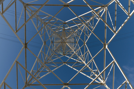 conduction: Electricity distribution tower seen from below on blue sky background -