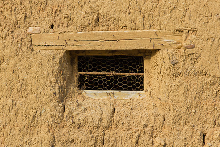 lintel: Small Window in old adobe house with wire mesh and wooden lintel